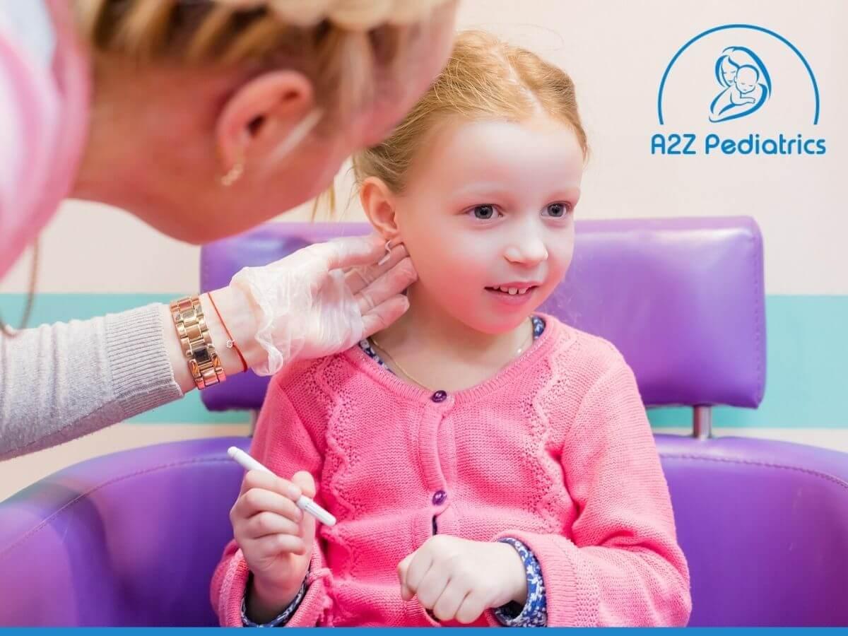 Cute little girl having ear pierced